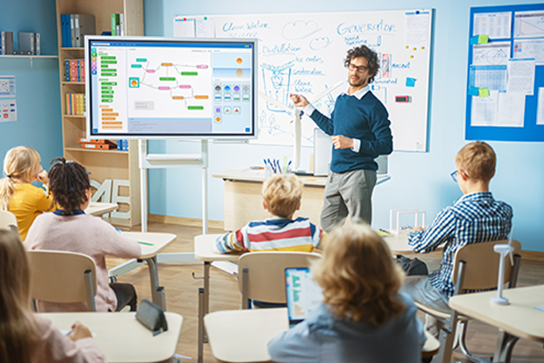 Primary School Teacher Uses Interactive Digital Whiteboard to Show Programming Logics to a Classroom full of Smart Diverse Children. Computer Class with Kids Listening